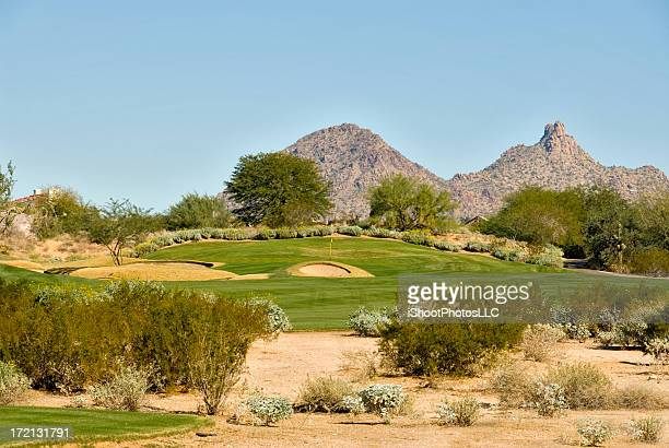 A golf course in a dry Arizona desert has greens and trees
