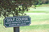 "A small sign telling pedestrians that access to a golf course is ""restricted to playing members and guests""."