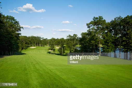 Golf fairway lined with trees near lake : Stock Photo