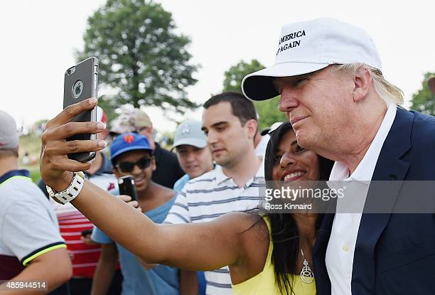 A golf fan takes a 'selfie' with presidential candidate Donald Trump during the final round of The Barclays at Plainfield Country Club on August 30...