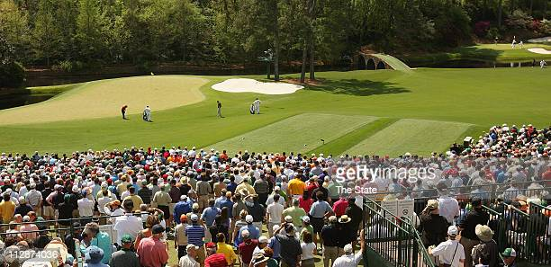 Golf fans gathered at holes 11 and 12 in Amen Corner to watch the second round of The Masters Tournament at Augusta National Golf Club in Augusta...