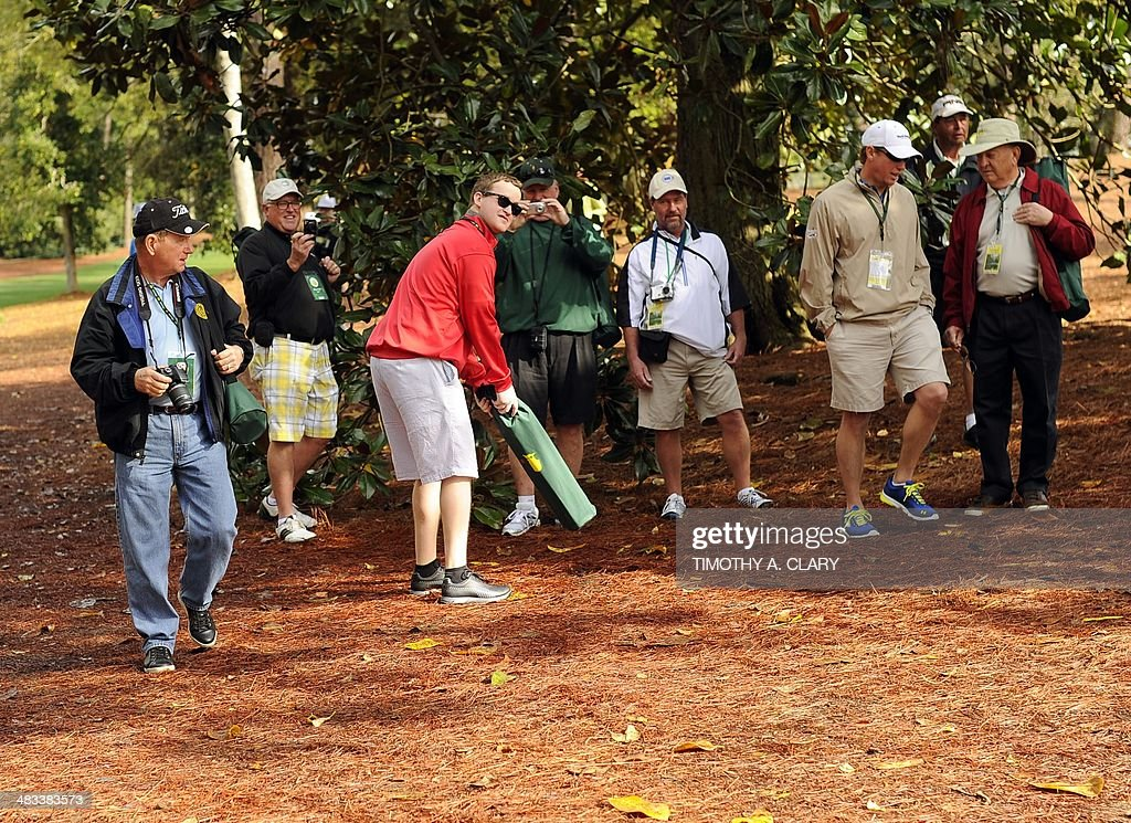 Golf fans pose for pics on the spot of US golfer Bubba Watson's shot on the 10th hole in the 2012 Masters playoff April 8, 2014 at Augusta National Golf Club in Augusta, Georgia. Watson was deep in the trees to the right of the fairway, 155 yards away, when he played a 40-yard hook with a wedge that landed about 10 feet beneath the hole. He two-putted for par to win the 2012 Masters. AFP PHOTO / Timothy A. CLARY