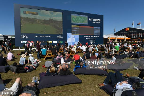 Golf fans watch the action on a big screen from giant beanbags in the tented village during the first round of the 146th Open Championship at Royal...