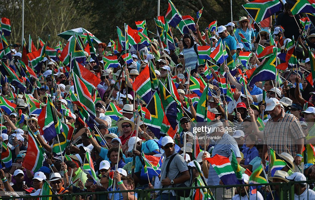 Golf fans wave South African flags in tribute to the late President Nelson Mandela after the final round of the Nedbank Golf Challenge at Gary Player CC on December 8, 2013 in Sun City, South Africa.