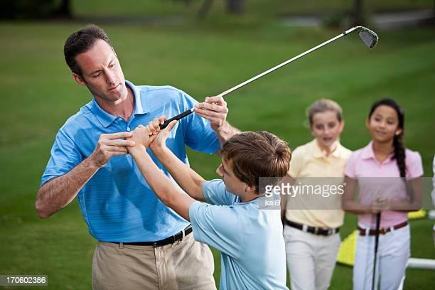 Golf instructor adjusting boy's grip