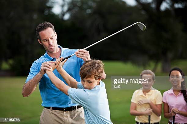 Golf instructor adjusting boy's grip