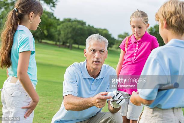 Golf instructor teaching class to young students