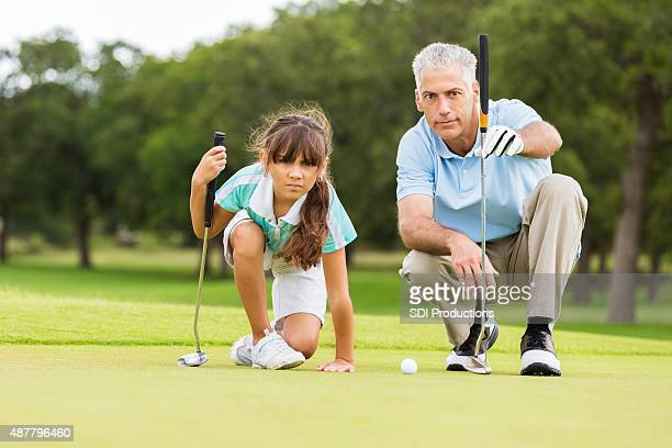 Golf instructor teaching technique to little girl
