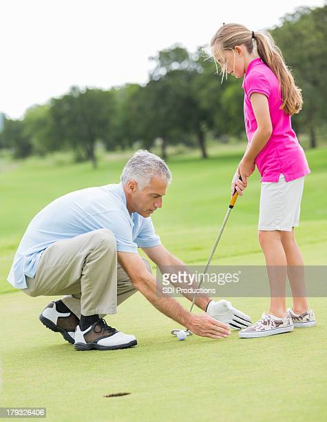 Golf instructor teaching young student golfer to stand while putting