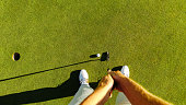 Pov shot of golf player at the putting green hitting ball into a hole. Personal perspective of professional golfer playing golf on field.