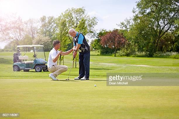 Golf pro teaching a senior male