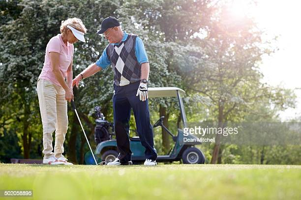 Golf pro teaching female golfer on putting green