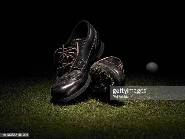 Golf shoes on lawn, ball in background