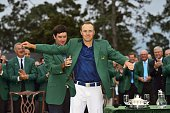The Masters Jordan Spieth victorious putting on green blazer with help from Bubba Watson during jacket ceremony after winning tournament on Sunday at...