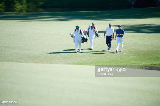 The Masters Phil Mickelson and Jordan Spieth walking on green with caddies during Saturday play at Augusta National Augusta GA CREDIT Robert Beck