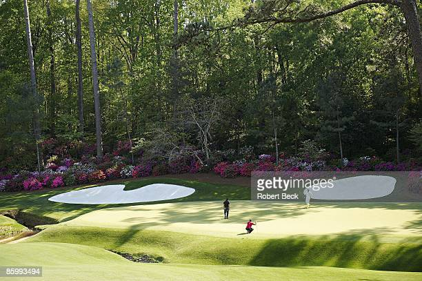 The Masters Scenic view of Tiger Woods lining up putt on No 13 green as Phil Mickelson watches during Sunday play at Augusta National Augusta GA...