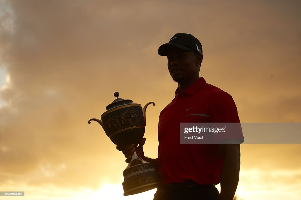 Silhouette view of Tiger Woods victorious with Gene Sarazen Cup trophy after winning tournament on Sunday at TPC Blue Monster Course of Doral Resort & Spa. Fred Vuich F190 )