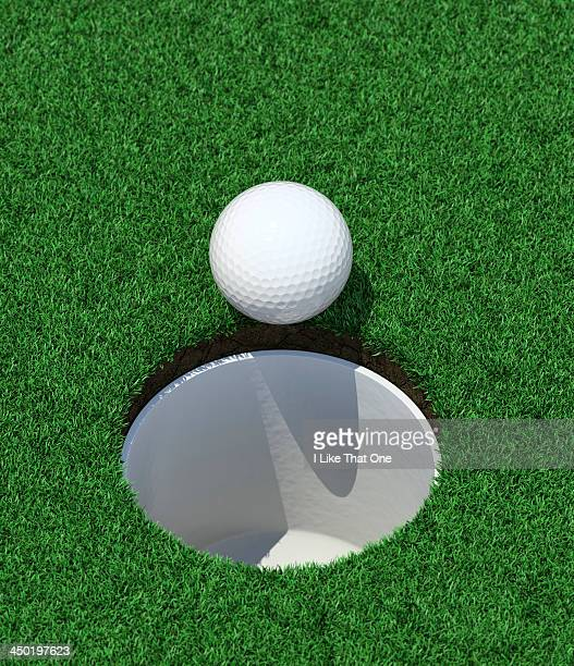 Golfball on the lip of the cup / golf hole