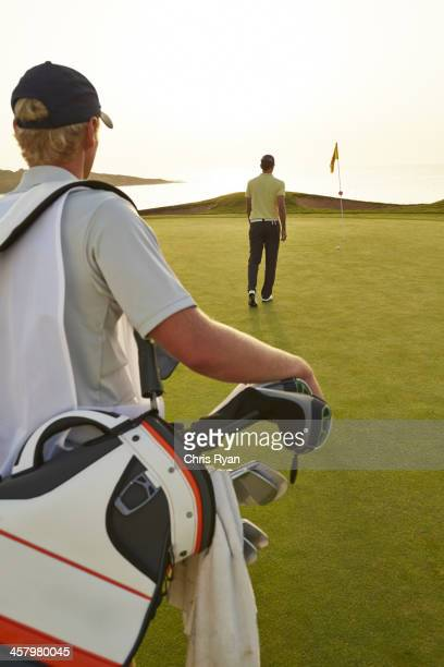 Golfer and caddy nearing golf flag