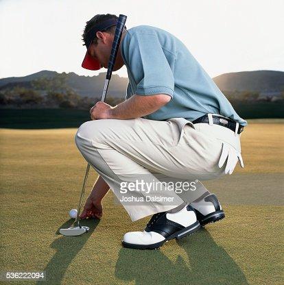Golfer applying ball marker : Stock Photo