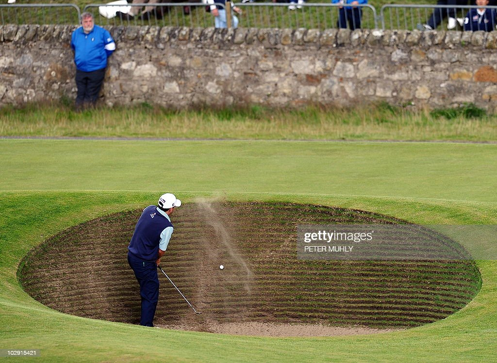US golfer Ben Curtis takes two attempts to escape the road hole bunker during his opening round on the first day of the British Open Golf...