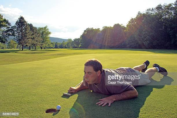 Golfer blowing air on golf ball