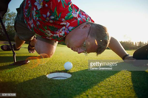 Golfer Blowing Ball Into Cup