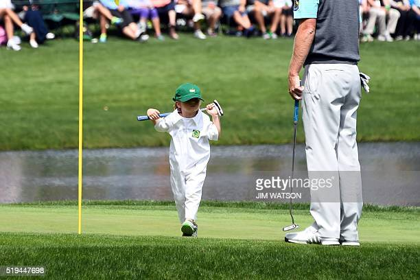TOPSHOT US golfer Brandt Snedeker's son Austin walks to his father on the 9th green during the Par 3 contest prior to the start of the 80th Masters...