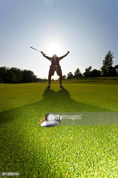 A Golfer celebrates as his golf ball sinks into the cup.