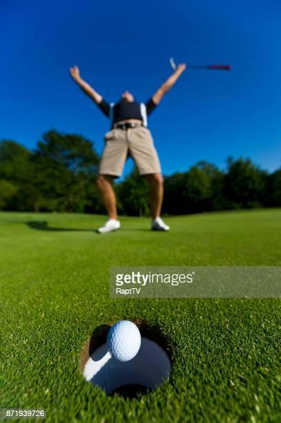 A Golfer Celebrates Sinking a Putt.