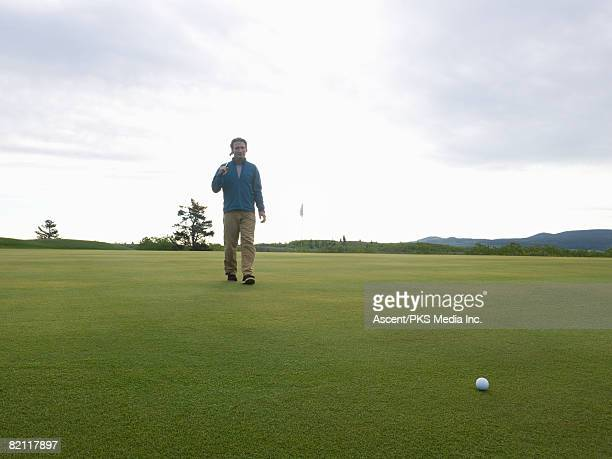 Golfer crossing putting green to ball