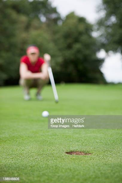 A golfer crouching down studying the distance to the hole, focus on hole