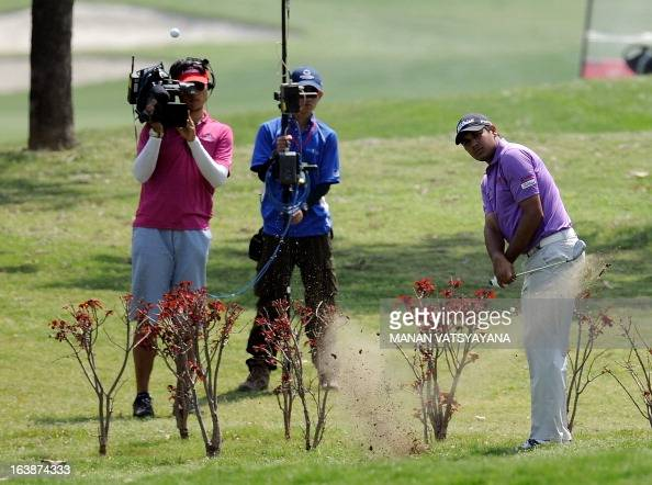 Golfer Gaganjeet Bhullar of India hits the ball out of a bush on the 8th green during the Avantha Masters golf tournament in Greater Noida on the...