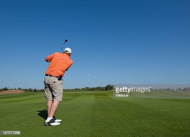 Golfer hits ball to green