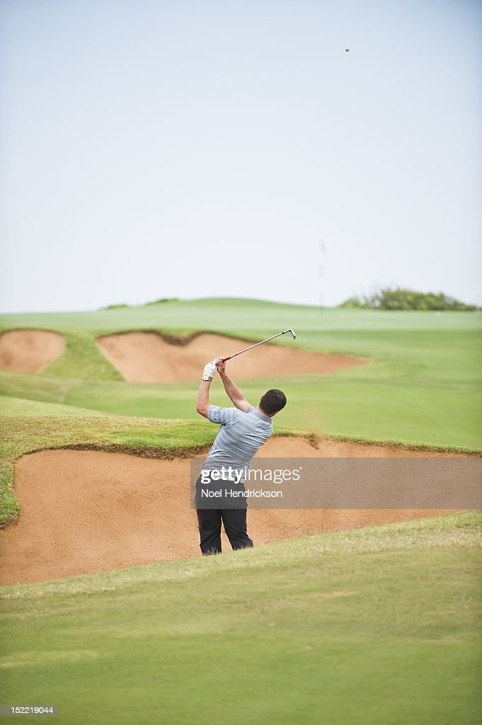 A golfer hits the ball out of the sand traps : Stock Photo