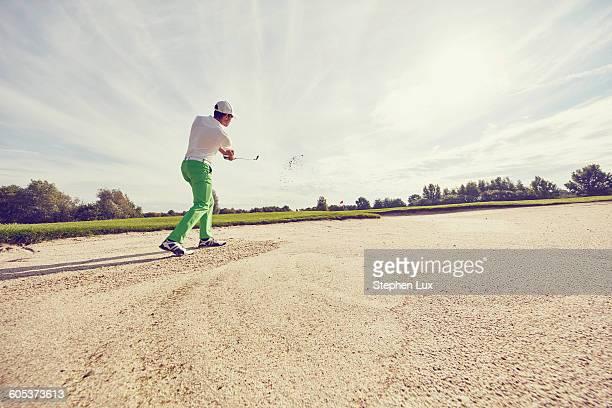 Golfer hitting ball in sand trap, Korschenbroich, Dusseldorf, Germany