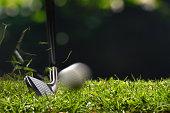 Golfer hitting golf ball with club on beautiful golf course