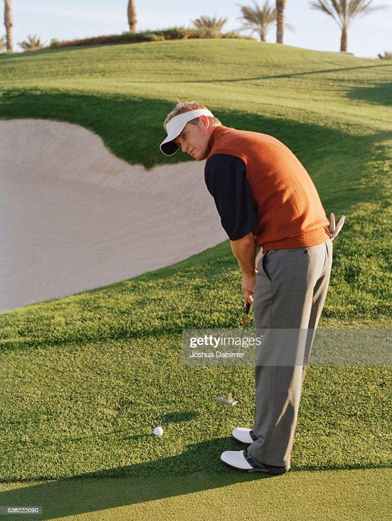 Golfer holding golf club : Stock Photo