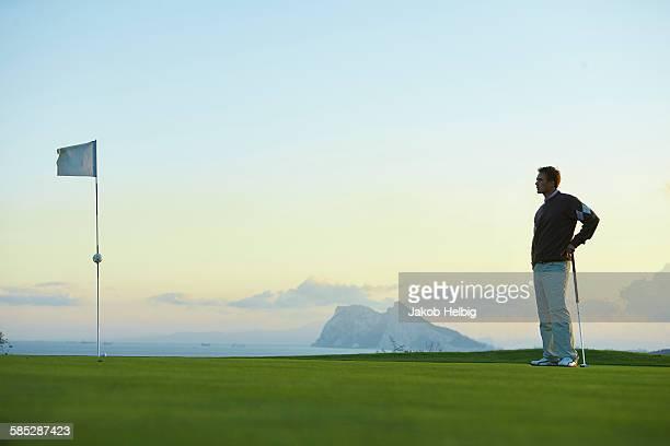 Golfer holding golf club standing near golf flag looking away