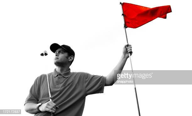 Golfer in black and white holding a red flag
