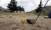 A golfer is about to hit the golf ball teeing off on the dirt at the Kabul Golf Club June 3 2005 in Kabul Afghanistan The Kabul Golf Club has been in...