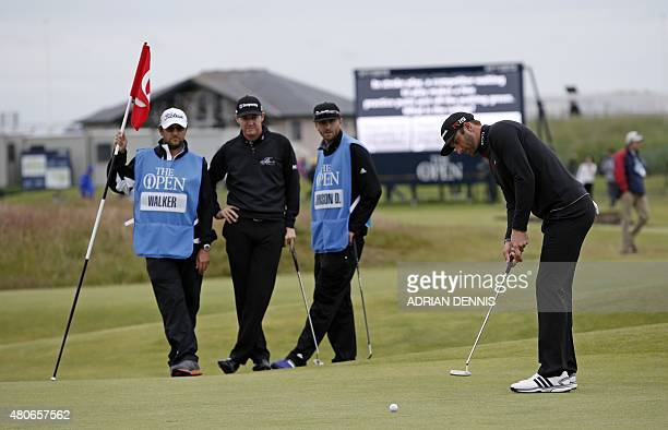 US golfer Jimmy Walker watches as US golfer Dustin Johnson putts on the 17th green during a practice round on The Old Course at St Andrews in...