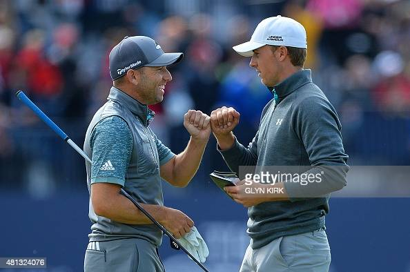 US golfer Jordan Spieth and Spain's Sergio Garcia have a fist pump on the 18th tee during their third rounds on day four of the 2015 British Open...