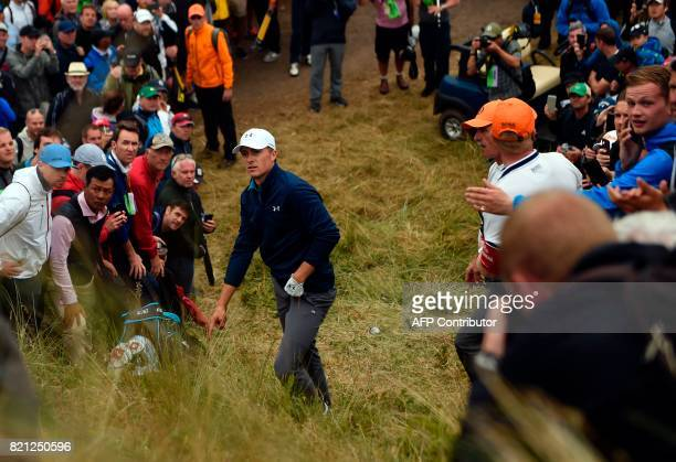 US golfer Jordan Spieth discusses his options with a rules official after taking a penalty drop for having an unplayable lie on the 13th hole during...