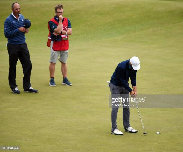 US golfer Jordan Spieth makes the final putt on the 18th green as US golfer Matt Kuchar looks on to win the Championship on day four of the 2017 Open...