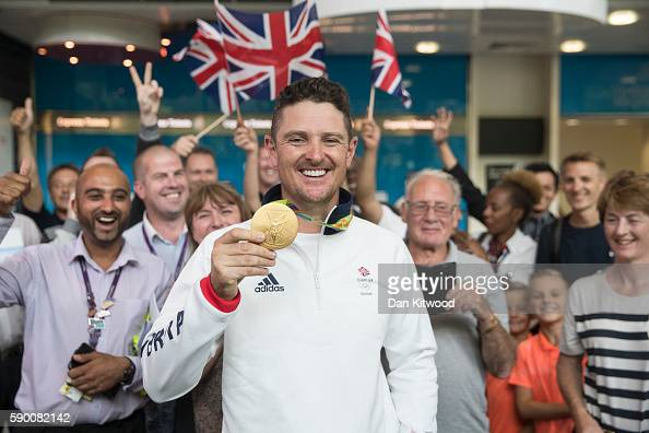Golfer Justin Rose of Great Britain poses with his Gold Medal after arriving on a British Airways flight from Rio de Janeiro in Brazil to London...