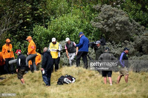 US golfer Justin Thomas and marshalls look for his ball on the 1st hole during his second round on day two of the Open Golf Championship at Royal...