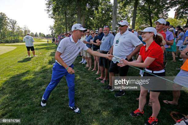 PGA golfer Justin Thomas gives a fan an autographed glove after she was hit with Justin's tee shot on the 15th hole during the Memorial Tournament...