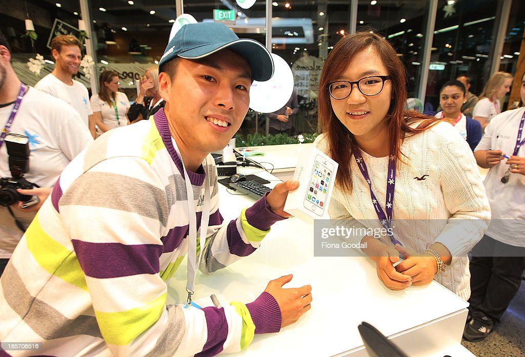 Golfer Lydia Ko presents the first in line Dion Zhang, (L) with his iPhone 5s at the Telecom New Zealand iPhone 5S launch event on October 24, 2013 in Auckland, New Zealand.