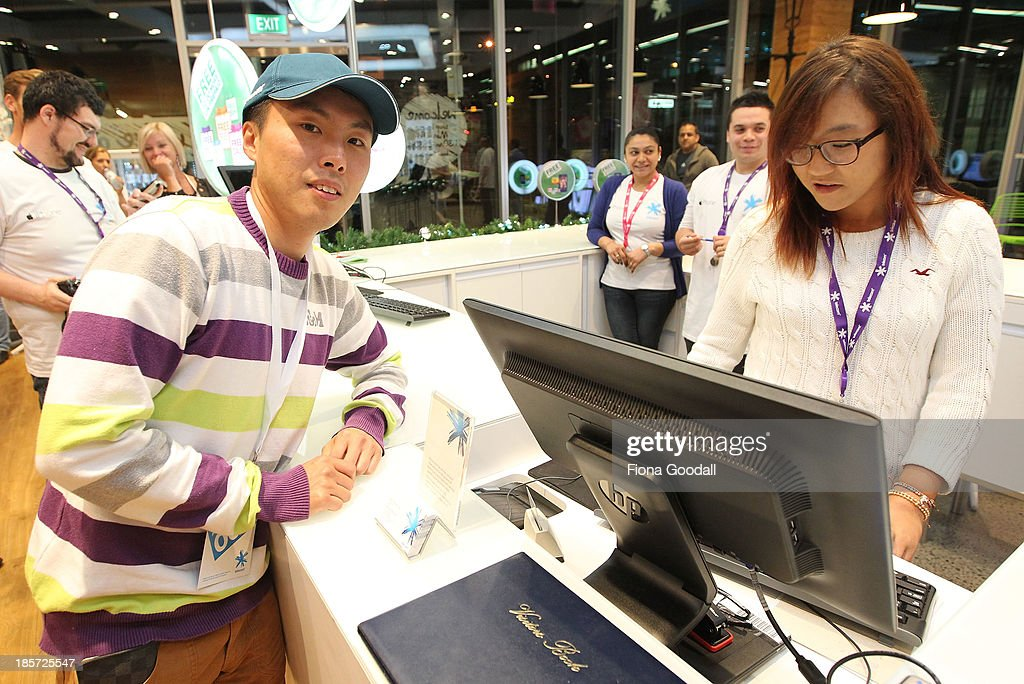 Golfer Lydia Ko sells the first iPhone 5s to Dion Zhang, (L) who was first in line at the Telecom New Zealand iPhone 5S launch event on October 24, 2013 in Auckland, New Zealand.